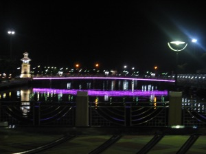 Bridge with colourful lights seen from a riverside restaurant